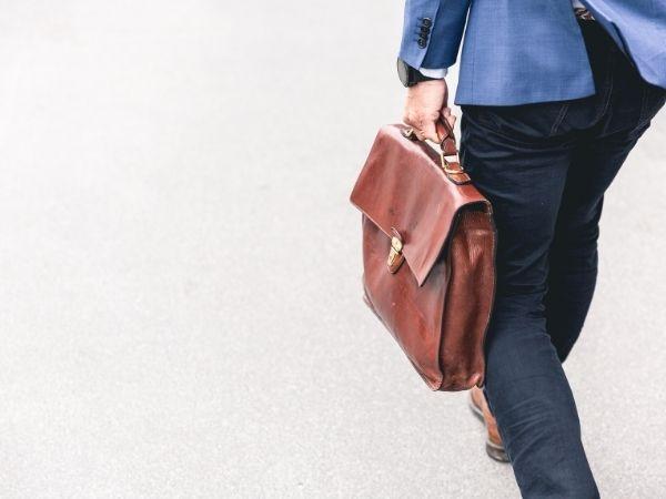 Nachteile Selbständigkeit: Mann trägt braune Aktientasche