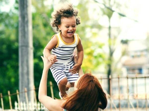 Einkaufen mit Kind: Frau wirft Kind in die Luft, das glücklich lacht.