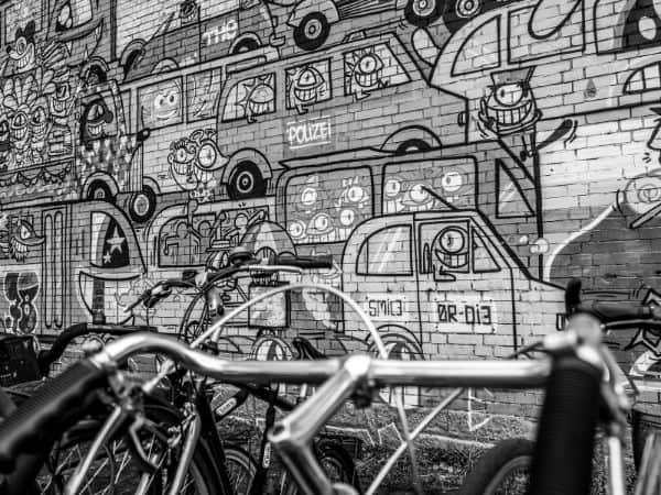 Fahrrad vor einer bemalten Wand mit Fahrzeugen