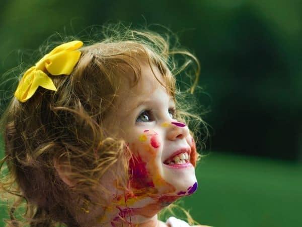 Was kostet ein Kind? Mädchen voller Körpermalfarbe schaut in den Himmel.