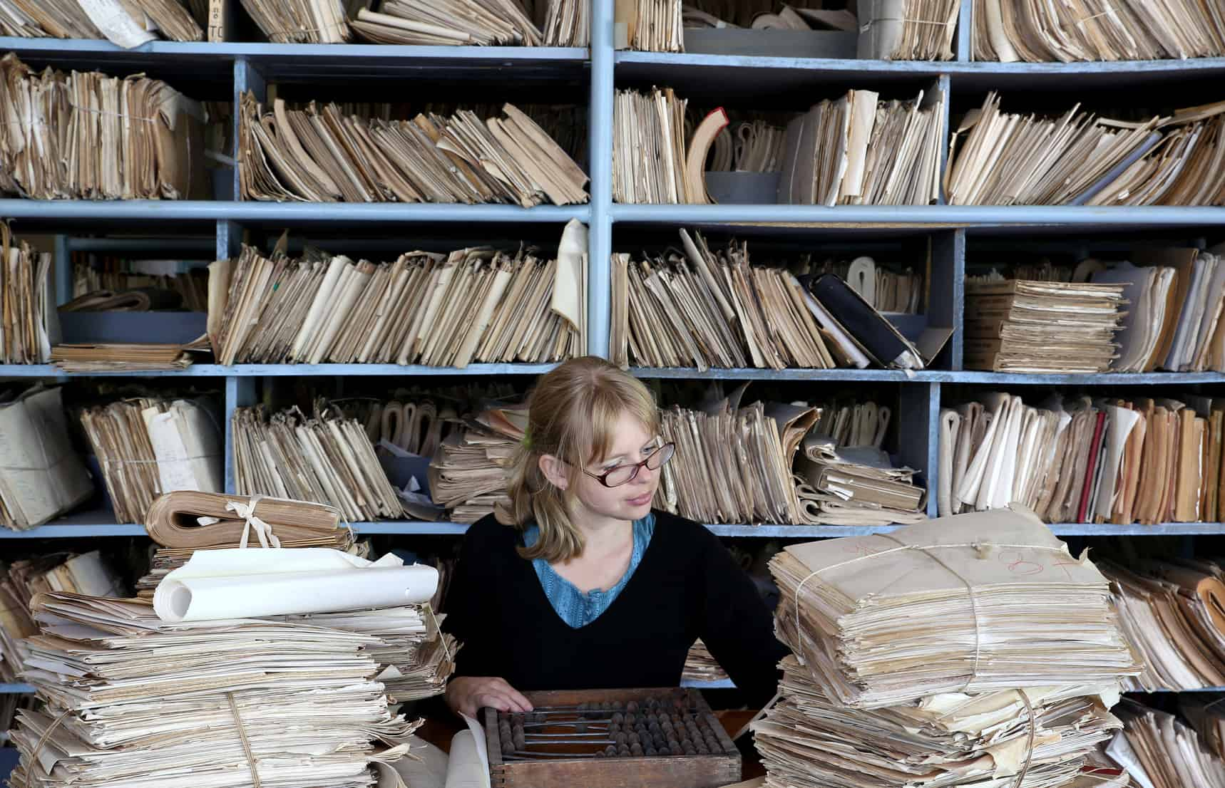 Frau sitzt zwischen Papierstapeln voller Finanzwissen