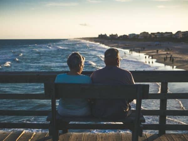 Die Rentenversicherungspflicht für Selbständige kommt. Ein Rentnerpaar sitzt auf einer Bank und schaut auf das Meer.