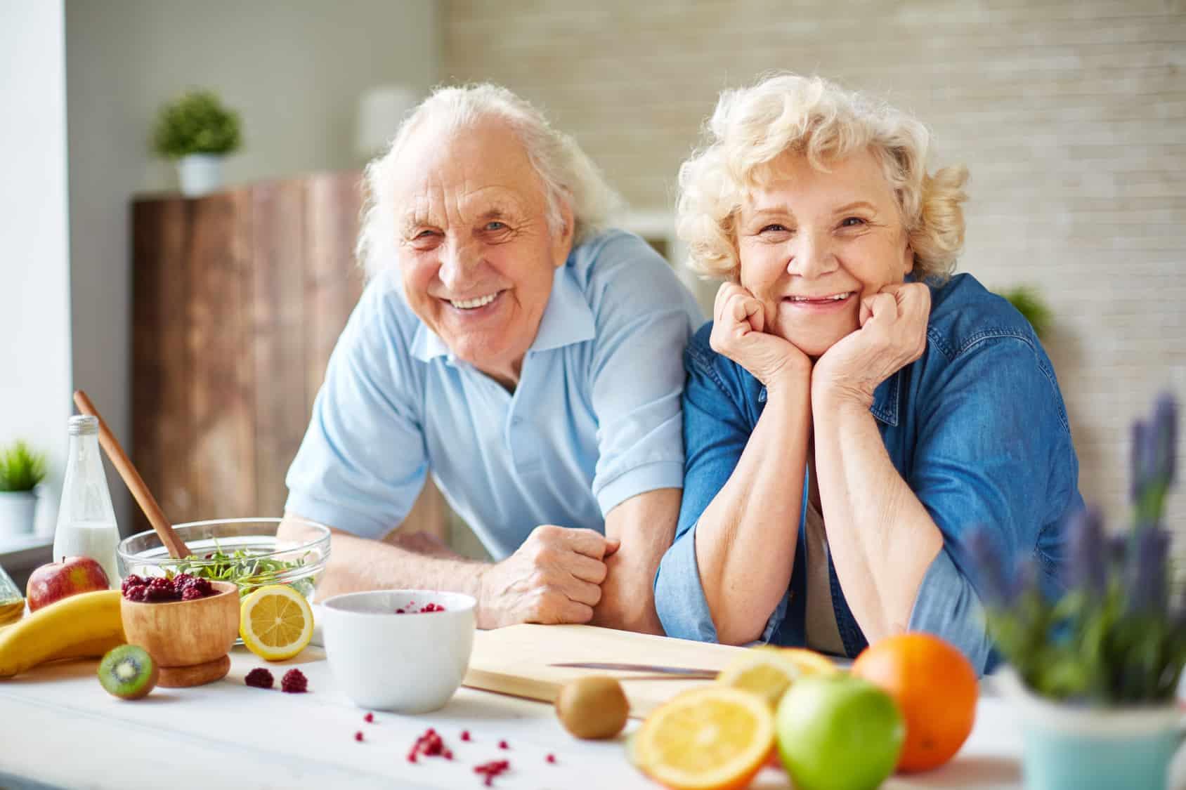 Glücklicher Rentner und Rentnerin am Küchentisch