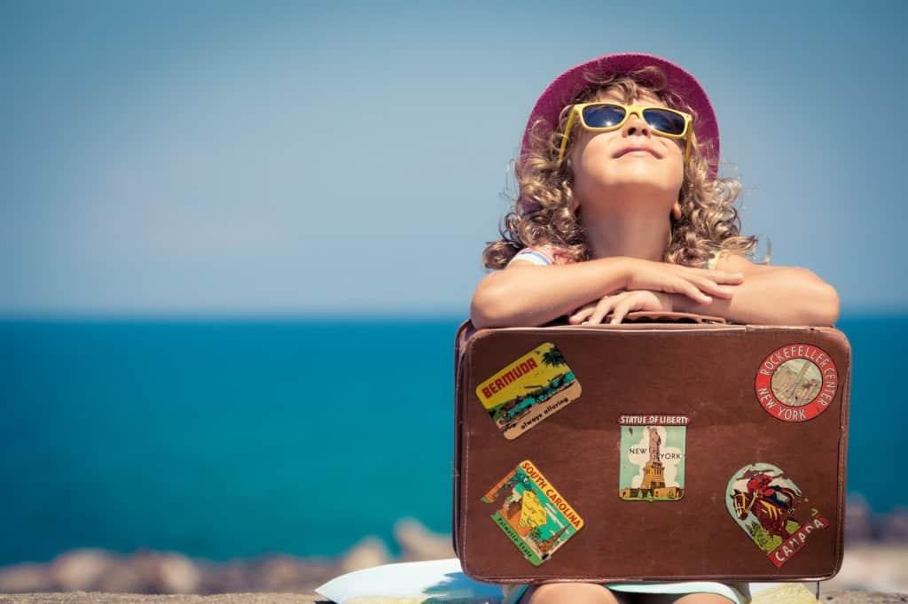 Das Ziel der finanziellen Freiheit ist überhöht. Ein Kind mit Reisekoffer, dass glücklich in den Himmel schaut. Interview mit Patrick Hundt